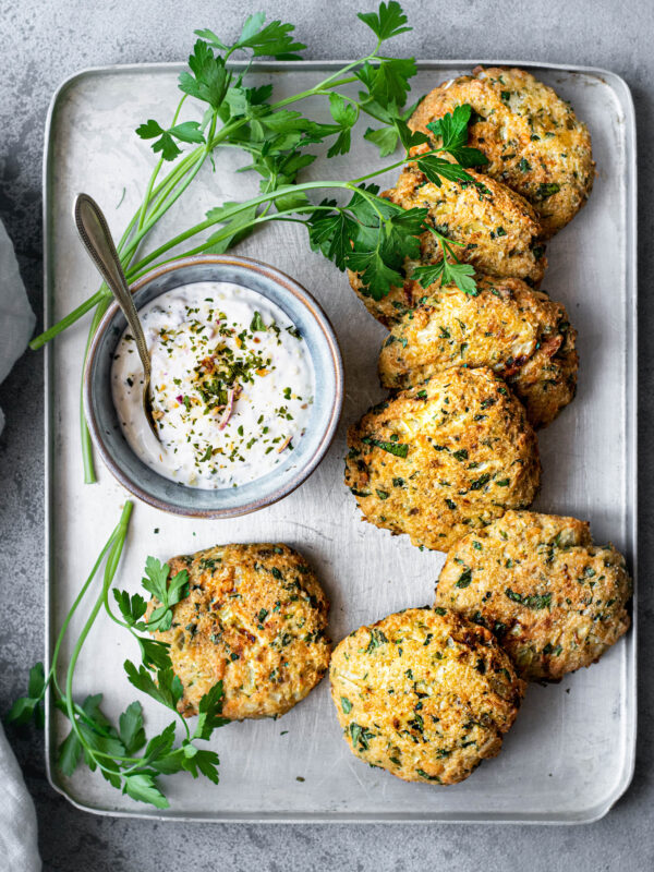Salmon cakes on a baking tray with sauce