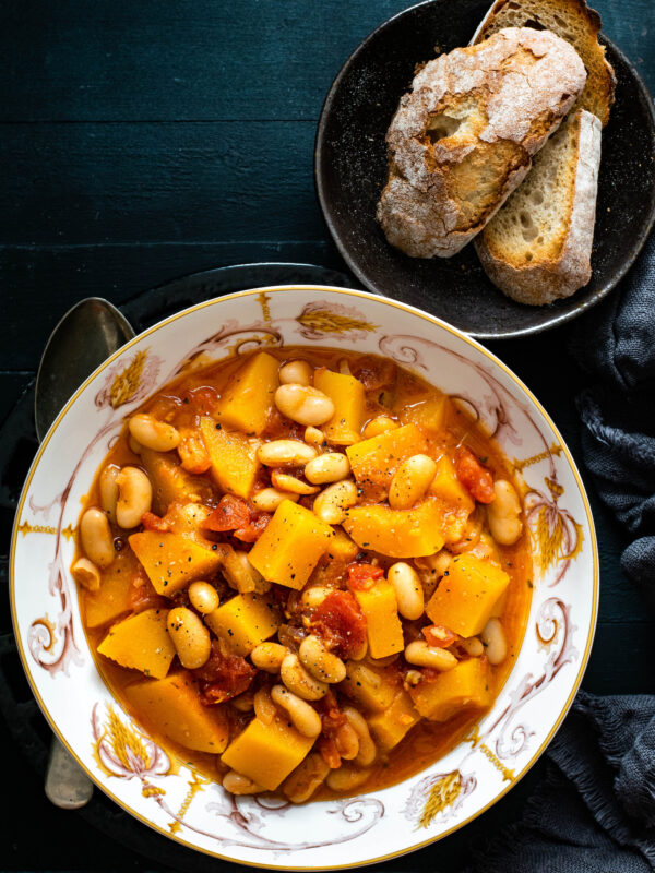 A bowl of butternut squash soup with sliced bread