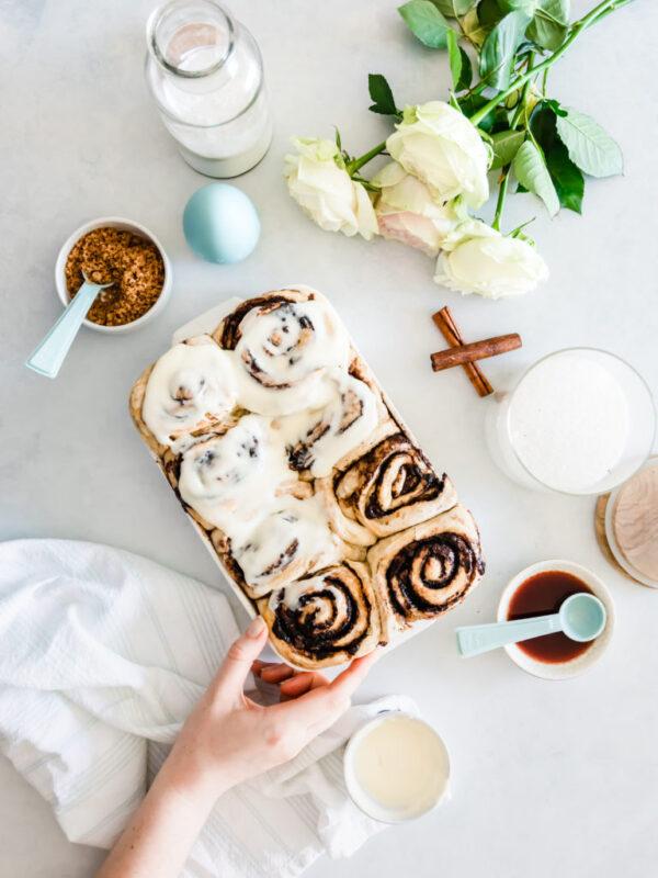 Hand taking a cinnamon bun from a baking dish