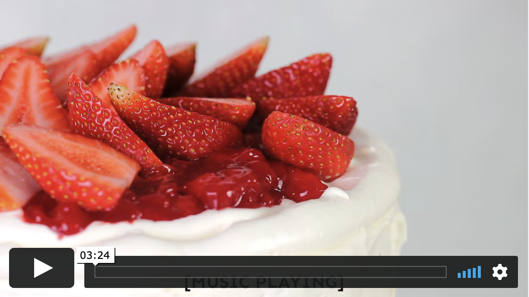 A white frosted cake topped with strawberries